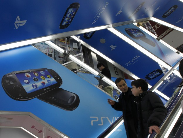 Shoppers walk past an advertisement board of Sony's PS Vita at an electronics shop in Tokyo