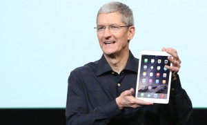 Apple CEO Tim Cook holds an iPad during a presentation at Apple headquarters in Cupertino